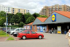 Supermarkt + Parkplatz - im Hintergrund Hochhäuser des Hamburger Stadtteils Steilshoop.