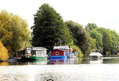 Hausboote auf der Doveelbe in Hamburg Allermöhe - hohe Bäume am Ufer des Hamburger Flusses.
