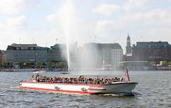 Das Fahrgastschiff ALSTERCABRIO mit Touristen und Fahrgästen voll besetzt auf der Hamburger Binnenalster - im Hintergrund die Alsterfontaine und der der Jungfernstieg