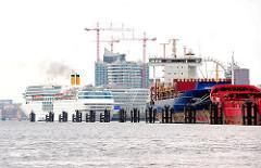 Blick über die Norderelbe zum Kreuzfahrtterminal Hafencity. An den Dalben im Fluss haben Auflieger festgemacht.