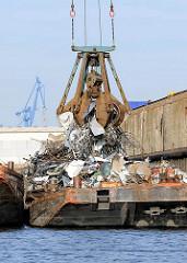 Schrottverladung am Rosskai im Hamburger Hafenstadtteil Steinwerder - ein Greifer mit einer Schrottladung belädt eine Schute am Kai.