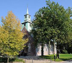Kirche in Nienstedten zwischen hohen Bäumen - die Fachwerkkirche ist eine der ältesten im Hamburger Raum.