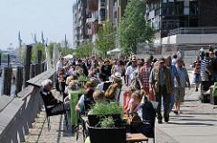 Sonnentag in Hamburg - Touristen besichtigen die Hamburger Hafencity - die Tische und Stühle der Aussengastronomie am Dalmannkai sind dicht besetzt.