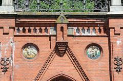 In die Ziegelfassade der Köhlbrandtreppe eingelassene Maskerons mit Merkur und Neptun - Bilder aus Hamburg Altona Altstadt.