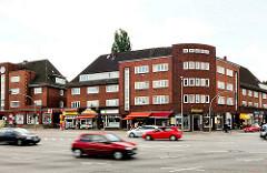 Blick über den Siemersplatz von Hamburg Lokstedt - mehrstöckige Backsteingebäude; Geschäfte.