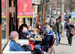 Strassencafe im Hamburger Szene Stadtteil Hamburg St. Georg. Werbung eigene Konditorei; Tische auf dem Fussweg in der Sonne.