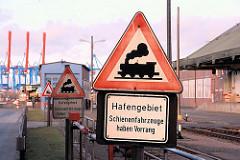 Schild Hafengebiet, Schienenfahrzeuge haben Vorrang - im Hintergrund die hochgefahrenen Ausleger der Containerkräne auf der anderen Seite der Süderelbe in Hamburg Altenwerder.