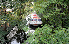 Fahrgastschiff Schleusenwärter auf dem Goldbekkanal in Hamburg Winterhude, schmaler Kanal zwischen Bäumen.