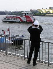 Blick von den St. Pauli Landungsbrücken auf die Elbe - eine Hafenfähre legt an. Zelt König der Löwen am anderen Elbufer.