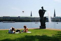Sommer in Hamburg - auf einer Liegewiese an der Binnenalster geniessen Hamburger das sommerliche Wetter und liegen in der Sonne.