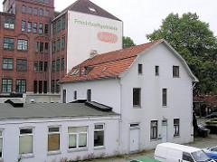 Alte Bebauung an der Jarrestrasse - einstöckiges Gebäude mit Lagerhaus auf dem Gewerbehof - im Hintergrund die Industriearchitektur einer ehem. Fabrik.