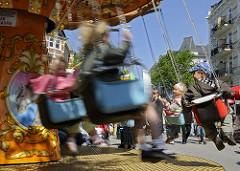 Kinderkarussell auf dem Strassenfest - Kinder haben Spass im drehenden Kettenkarussell am Strassenrand der Hamburger Osterstrasse.