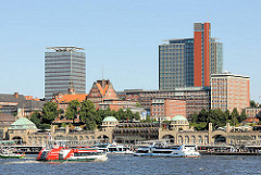 Panoram der St. Pauli Landungsbrücken -  eine Hafenfähre fährt zum Anleger - Fahrgastschiffe am Ponton - Hochhäuser auf Hamburg St. Pauli.