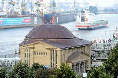 Mit Kupfer gedeckte Kuppel des Eingangs zum Alten Elbtunnel - ein Frachtschiff verlässt den Hamburger Hafen.