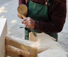 Bildhauer bei der Arbeit - Holzskulptur mit Beitel und Vollholzhammer.