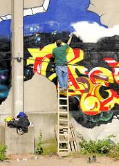 Sprayer bei der Arbeit auf einer Leiter - entstehen eines Grafittis an einer Gebäudewand in der Hafencity Hamburg.