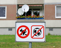 Verbotsschild - kein Fussballspiel, keine freilaufenden, kackende Hunde - Balkon mit Geranien und Satelittenschüsseln im Hintergrund - Fotos aus Hamburg Osdorf.
