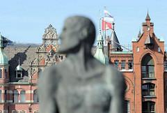Denkmal des sagenumwobenen Seeräubers Klaus Störtebeker, 1402 geköpft auf dem Grasbrook. Im Hintergrund neogotische Backsteingiebel der Speicherstadt und dem Speicherstadt Rathaus, dem Sitz der HHLA.