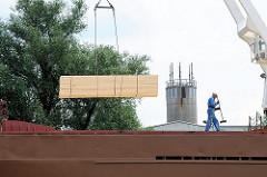 Verladung von Stückgut am Wilhelsburger Reiherstieg - mit dem bordeigenen Kran wird ein Stapel Holzbretter an Bord gehievt.