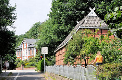 Fachwerkhaus mit Ziegeldach - im Hintergrund ein Wohnhaus in Gründerzeit-Archtektur.