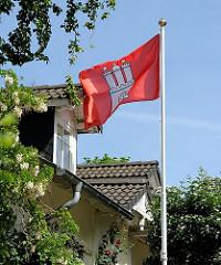 Eine Hamburg Fahne weht im Wind in einem Vorgarten von Blankenese.