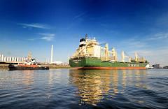Das Frachtschiff RICKMERS TOKYO in der Rethe von Hamburg Wilhelmsburg - im Hintergrund Industrieanlagen.