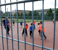 Fussballfeld mit fussballspielenden Kinder in Hamburg Neuallermöhe - der Platz ist mit einem Gitter geschützt.