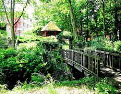 Holzbrücke über die Schillingsbek in Hamburg Lokstedt - Pavillon mit Reet gedeckt steht in hohem Farn.