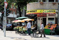 Obst und Gemüsegeschäft - Balkan Market - mit Auslagen an der Jarrestrasse und Grossheidestrasse; Spaziergänger mit Kinderwagen.