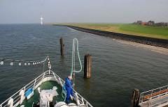 Ankunft der Cuxhafen-Neuwerk-Fähre am Anleger der Insel. Ein Schiffer bereitet das Anlegemanöver vor.