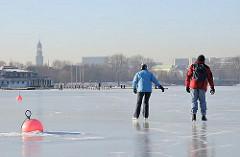 Schlittschuhlaufen auf dem Alstereis am Alsterufer von Hamburg St. Georg. Im Eis festgefroren eine Schwimmboje.