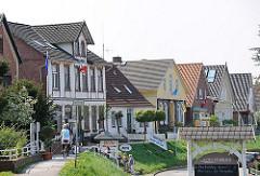 Häuser am Deich in HH-Cranz - Touristen fahren Rad auf der Deichkrone.