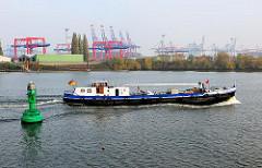 Blick über das Köhlfleet nach Hamburg Waltershof und den Containerkränen vom Eurogate Terminal - ein Tankschiff fährt Richtung Dradenauhafen - vorne lks. eine grüne Fahrwassertonne.