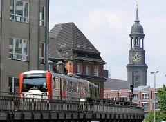 U-Bahn auf dem Hochbahnviadukt beim Rödingsmarkt, Mönkedammfleet / HH-Altstadt - im Hintergrund der Turm der St. Michaeliskirche.
