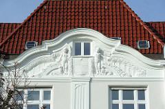 Fassadenschmuck und roten Dachziegeln - Putten mit Jugendstil Ornamente.