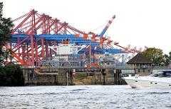 Blick auf die alte, gesperrte Rugenberger Schleuse, die zum Rugenberger Hafen und Waltershofer Hafen führte - im Hintergrund die Containerkräne vom Terminal EUROGATE.