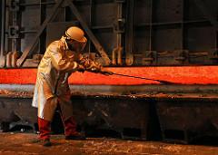 Arbeiter in Schutzkleidung am glühenden Schmelztiegel des Alumiumwerks in Hamburg - Bilder aus den Hamburger Stadtteilen - Fotos der ansässigen Industrie, Industriefotografie.