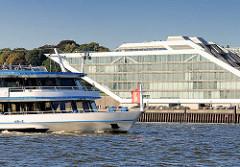 Ein Fahrgastschiff mit Hamburgflagge auf der Elbe vor Hamburg Altona Altstadt - am Ufer das Bürogebäude Dockland.
