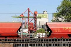 Güterzug mit Loren auf den Gleise über der Reiherstiegschleuse in Hamburg Wilhelmsburg - im Hintergrund Gebäude und Krananlagen am Wilhelmsburger Reiherstieg.