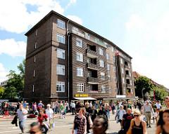 Wohngebäude / Etagenhaus mit Klinkerfassade - Menschen überqueren die Strasse beim Bahnhof Hasselbrook.