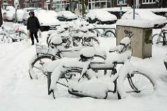 Hoch eingeschneite Fahrräder am Strassenrand in der Jarrestadt von Hamburg Winterhude.