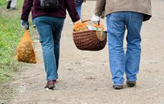 BesucherInnen des Kartoffelmarkt auf dem Biohof Wulksfelde tragen ihre Ernte zum Auto.