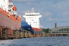 Schiffe an den Dalben in der Norderelben und ein Ausschnitt der Freihafenelbbrücken - dahinter der historische Wasserturm von Hamburg Rothenburgsort.