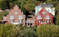 Wohnhäuser mit Klinkerfassade am Ufer der Elbe in Hamburg Nienstedten - rotes Weinlaub an der Hausfassade.