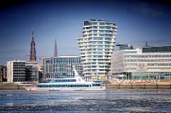 Architektur der Hamburger Hafencity - Kirchturmspitzen hinter den modernen Neubauten den neuen Hamburger Stadtteils - Fahrgastschiff auf der Norderelbe.