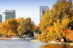 Bunt gefärbte Herbstbäume an der Hamburger Alster - ein Alsterdampfer fährt durch die Lombardsbrücke in die Binnenalster; Hamburgbilder.