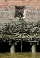 Verwitterte Ziegelmauer / Kaimauer; an einem Eisenring hängt ein ein altes Tau. Bei Ebbe sind die Eichenpfähle zu erkennen, auf denen die Kaianlage gegründet ist.