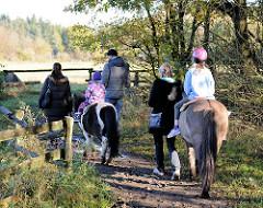 Kinder reiten auf Ponys des Ponyhofs im Niendorfer Gehege auf dem Reitweg entlang der Pferdewiese - Fotos aus den Stadtteilen der Freien und Hansestadt Hamburg.