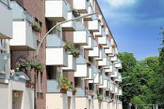 Hausfassade an der Georg Thielen Gasse in der Hamburger Jarrestadt. Blühende Pflanzen hängen an den weissen Balkons.