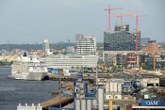 Hinter den Industrieanlagen am Kirchenpauerkai der Norderelbe die Baustelle der Elbphilharmonie - ein Kreuzfahrtschiff liegt am Hamburger Cruisecenter der Hafencity.
